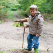 Stock Photo: Little boy with wellies plaing in wood