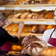 Saleswoman in bakery in front of shelves — Stok fotoğraf