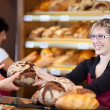 Friendly saleswoman in bakery passing bread — Stock Photo #26164111