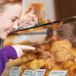 Woman Selecting Bread From Display Cabinet — Stock Photo #26164149