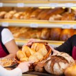 Worker Giving Breadbasket To Female Customer — Stock Photo #26165079