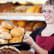 Saleswoman holding a tray of bread rolls — Stock Photo