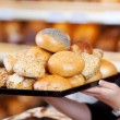 Woman holding various bread rolls in a bakery — Stock Photo #26165609