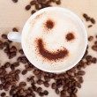 Smiley Face In Cappuccino With Coffee Beans On Table — Stock Photo #26165635