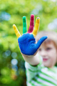 Boy showing his colorful painted hand in the garden — Stock Photo