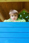 Young cheerful boy inside a blue playhouse — Stock Photo