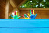 Childrin showing colorful painted hands — Stock Photo