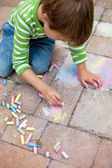 Boy playing with chalk on pavement — Stock Photo