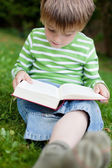 Boy sitting on green grass and reading — Стоковое фото