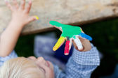 Sweet little boy showing his colorful hand — Stock Photo