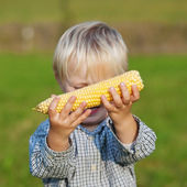 Young boy showing corn on the cob — Stock fotografie