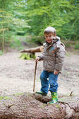 Little boy with wellies plaing in the wood — Stock Photo