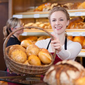Smiling woman passing basket of breads — Stock Photo