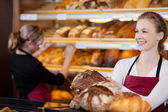 Saleswoman in bakery in front of shelves — Stock Photo