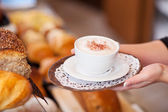 Saleswoman passing cappuccino over the counter — Stock Photo