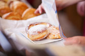 Saleswomanwrapping pastry in paper — Stock Photo