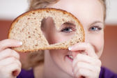 Woman Looking Through Heart Shaped Hole In Bread — Stock Photo