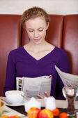 Woman reading newspaper in cafe — Stock Photo