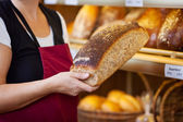 Bakery Worker Holding Bread Loaf By Display Cabinet — Stock Photo