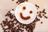Smiley Face In Cappuccino With Coffee Beans On Table — Stock Photo