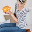 Woman Looking At Piggybank While Sitting On Suitcase In Bed — Stok fotoğraf