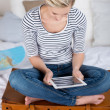 Stock Photo: WomSitting On Overloaded Suitcase While Using Digital Tablet