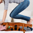 Cheerful Woman Packing Suitcase On Bed — Stockfoto