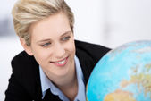 Businesswoman Looking At Globe In Office — Stock Photo