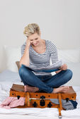 Woman Sitting On Overloaded Suitcase While Reading A Map — Stock Photo