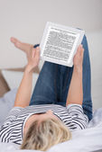 Woman Reading Ebook While Lying On Bed — Stock Photo
