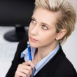 Blond Businesswoman Thinking At Office Desk — Stock Photo