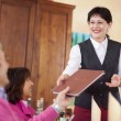 Cheerful waitress passing the menu to guest — Stock Photo