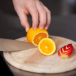 Stock Photo: Chef's Hand Cutting Orange For Garnishing