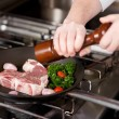 Stock Photo: Cook seasoning meat with pepper