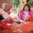 Waitress pouring red wine at guests glasses — Stock Photo