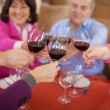 Stock Photo: Elderly friends saying cheers with red wine