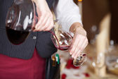 Waitress Pouring Red Wine In Wineglass From Decanter — Stock Photo