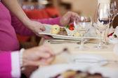 Los camareros mano plato de servir a los clientes en el restaurante de mesa — Foto de Stock