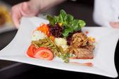 Chefs mãos segurando um prato delicioso — Foto Stock