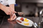 Tamizado del polvo de coco en la placa en el mostrador de la cocina de la mano de los chefs — Foto de Stock