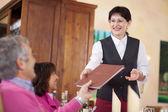Camarera alegre pasando el menú a la huésped — Foto de Stock