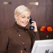 Cheerful female receptionist using telephone — Stock Photo