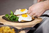 руки шеф-повара, размещение жареное яйцо на блюдо на кухне счетчик — Стоковое фото