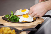 Chef's Hands Placing Fried Egg On Dish At Kitchen Counter — 图库照片