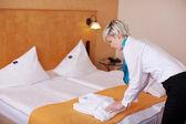 Female Housekeeper Keeping Bathrobe On Bed — Stock Photo