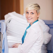 Housekeeper Stacking Sheets In Stock Room — Stockfoto