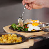 Chef's Hand Pouring Sauce On Egg Dish In Kitchen — Stock Photo