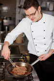 Young cook preparing steak in a pan — Stock Photo