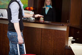 Costumer ringing bell at hotel counter — Stock Photo