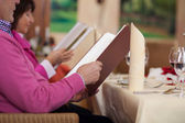 Couple in restaurant reading the menu — Stock Photo